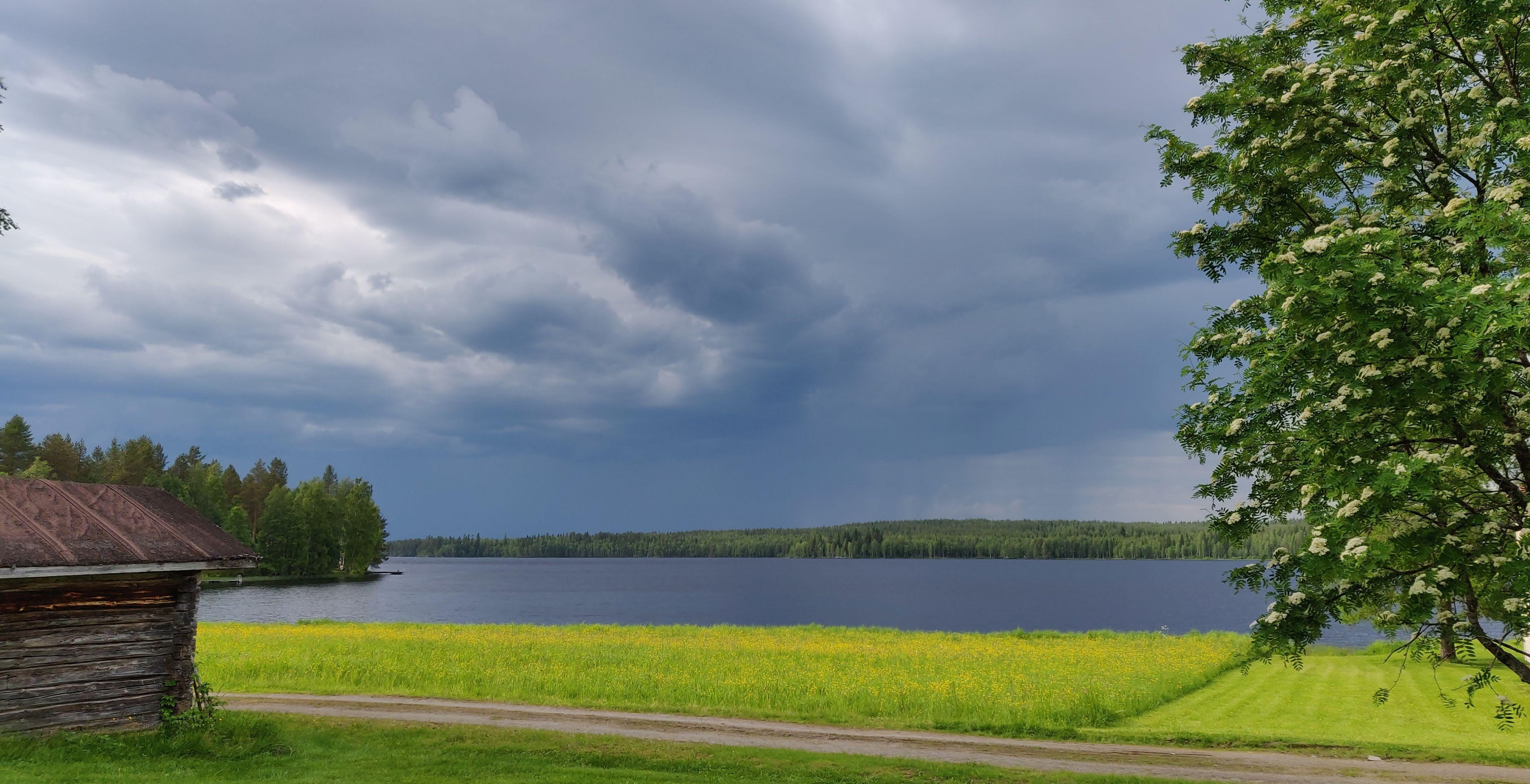 Kuvassa näkyy maalaismaisema, jossa on järvi ja vanha rakennus